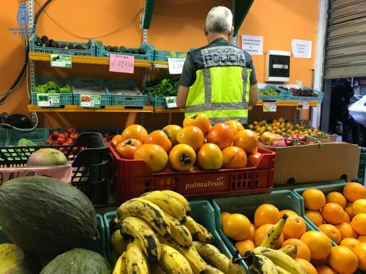 Un agente de la Policía inspecciona la frutería donde se vendía droga.