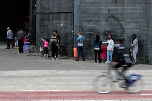 Varias personas hacen cola para recoger alimentos durante el reparto que ha realizado el Banco de Alimentos en el campo de Mestalla.