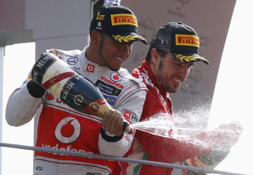 El piloto de McLaren Leweis Hamilton (i) y el de Ferrari Fernando Alonso (d), celebran el podio en el Gran Premio de Italia.