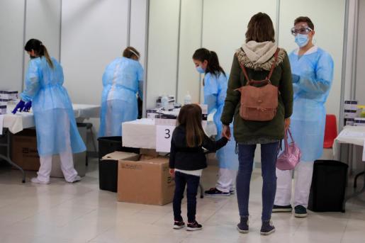 Una madre con su hija en el Centro Cultural Tomás y Valiente de Fuenlabrada donde el gobierno regional realiza test de antígenos a los vecinos de la localidad.