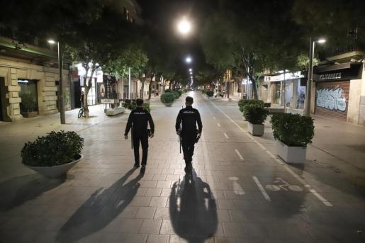 Agentes de la Policía Nacional patrullan por la calle Blanquerna durante la primera noche del toque de queda.