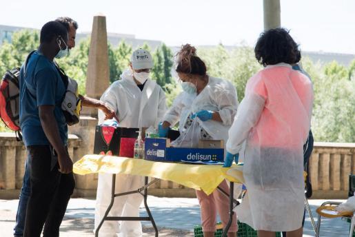 Voluntarios de la Fundación Arrels repartían comida a temporeros del campo en julio, por un brote originado en Lleida ciudad y seis municipios más de la comarca del Segrià.
