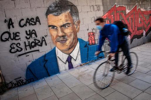 Una persona en bicicleta en Valencia pasa frente a una pintura mural del artista urbano J.Warx donde aparece el presidente del Gobierno, Pedro Sánchez.