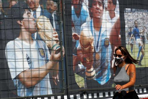 Una mujer pasea junto a varios carteles que rememoran la gesta de Diego Maradona en el Mundial de México cuando se cumple el 60 aniversario del futbolista argentino.