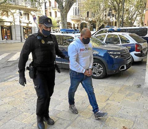 El acusado, custodiado por un policía, en la Audiencia.