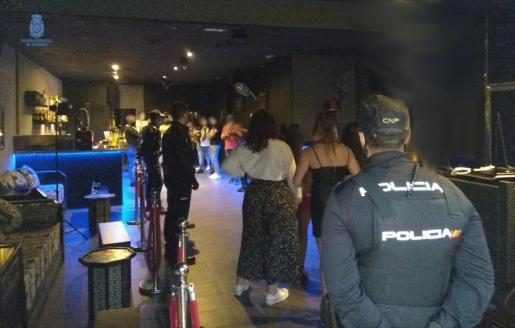 Agentes de la Policía Nacional junto a los jóvenes que participaron en la fiesta ilegal.