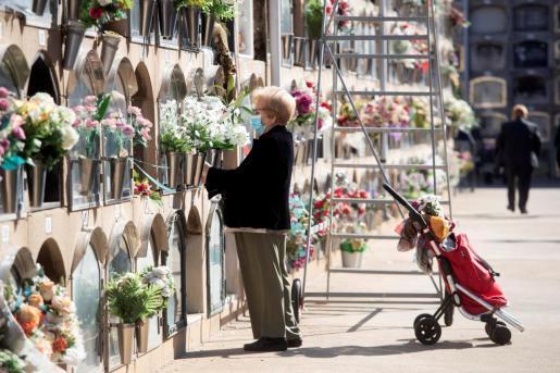 Una mujer visita la tumba de sus familiares en el cementerio de Poblenou en Barcelona este sábado en la víspera del día de Todos Los Santos.