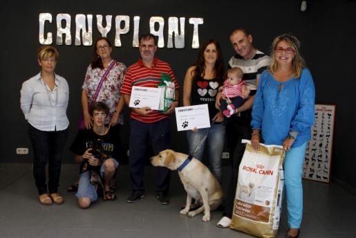 Los dos perros ganadores junto a sus familias, con Fina Costa, directora del Club del Suscriptor a la derecha, y Begoña, encargada de la tienda, la primera por la izquierda.
