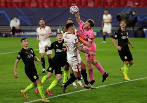 El portero del Krasnodar Ayvey Safonov intenta despejar ante el centrocampista argentino del Sevilla Lucas Ocampos.