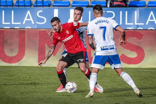 Dani Rodríguez, centrocampista del Mallorca, entre dos futbolistas del Real Zaragoza.