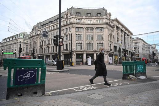 Una mujer camina por una inusual Oxford Street en Londres.