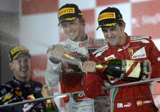 FRA42 SINGAPUR (SINGAPUR), 23/9/2012.- El piloto español de Fórmula Uno Fernando Alonso (d), de Ferrari, el británico Jenson Button (c), de McLaren Mercedes, y el alemán Sebastian Vettel (i), de Red Bull Racing, se rocían con champán en el podio del Gran Premio de Singapur en el circuito nocturno de Marina Bay en Singapur hoy, domingo 23 de septiembre de 2012. Vettel ganó la carrera, Button finalizó en segunda posición y Alonso fue tercero. EFE/Franck Robichon     SINGAPUR AUTOMOVILISMO GP SINGAPUR