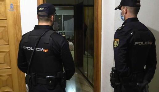 Dos policías nacionales, en la puerta de un domicilio.