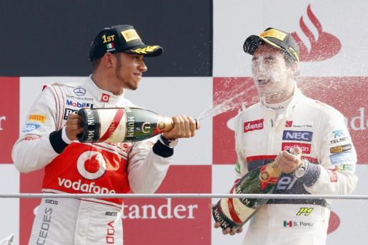 Lewis Hamilton, a la izquierda, celebrando uno de sus triunfos.