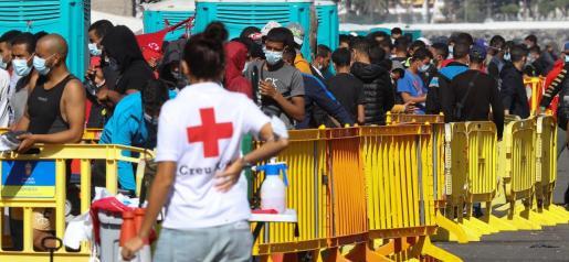 Una voluntaria de Cruz Roja junto a varios inmigrantes este jueves en el muelle de Arguineguín.