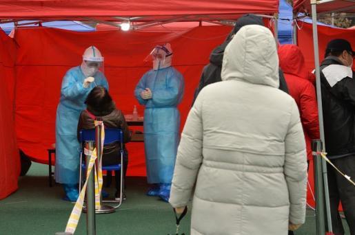 Varios sanitarios hacen pruebas de COVID en China.