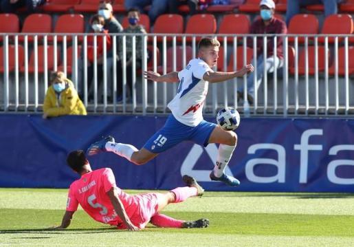 El jugador del Rayo Majadahonda Raúl Sánchez supera la entrada del defensa del Poblense Calonge en un lance del partido que ha enfrentado a ambos equipos en el Cerro del Espino en Madrid.