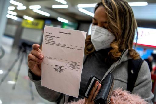Una pasajera procedente de un vuelo de Colonia (Alemania) muestra el resultado negativo de su PCR, este lunes, tras aterrizar en el Aeropuerto de Palma.