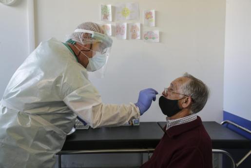 Un sanitario toma una muestra a un paciente para la realización de una prueba PCR.