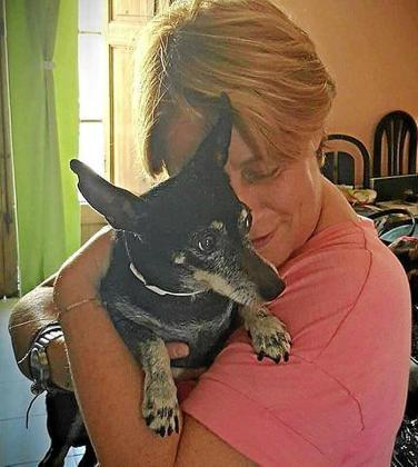 Marita Bauzá, una impulsora del Proyecto Abuelos Mallorca, abraza a un perro anciano rescatado.