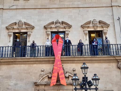 Las autoridades, en el balcón del Cort, junto al lazo que simboliza este lunes la lucha contra el sida.