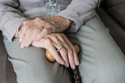 Una mujer sostiene su bastón.