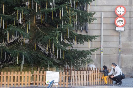 Un hombre con un niño en el árbol de Navidad de la plaza de Sant Jaume de Barcelona.