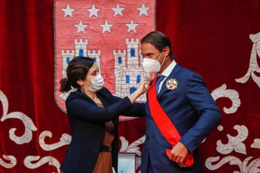 La presidenta de la Comunidad de Madrid, Isabel Díaz Ayuso (i) entrega al tenista Rafael Nadal (d) la Gran Cruz de la Orden del Dos de Mayo.