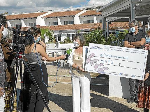 La presidenta de la Asociación Elena Torres mostrando el cheque con la recaudación de Oktober Pink.