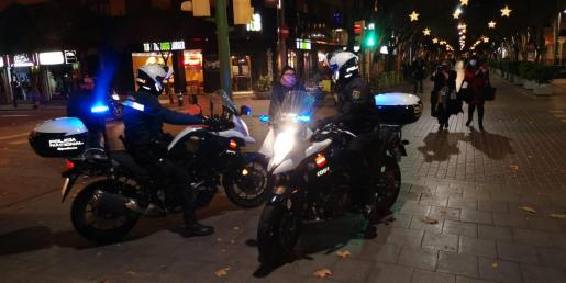 Agentes de la Policía Nacional controlando una calle de Palma e informando a la gente del nuevo horario del toque de queda, que desde este jueves es a partir de las 22:00 horas.