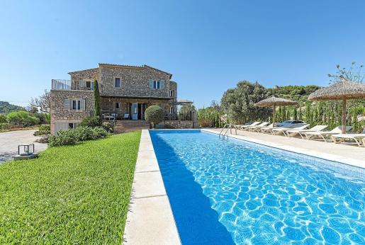 Una gran piscina larga, perfecta para practicar la natación, se abre junto al precioso porche con zona de estar y comedor exterior.