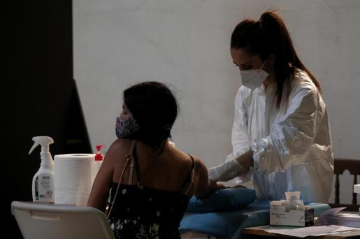 Una sanitaria sacando una muestra de sangre a una mujer.