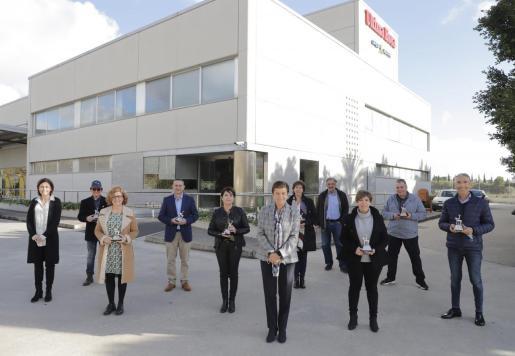 Los ocho trabajadores que han recibido el Siurell de Plata posan junto a Carmen, Paula y Miquel Serra.