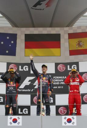 El pilot de Red Bull Sebastian Vettel (c) celebra su victoria en el Gran Premio de Corea junto a su compañero de equipo, Mark Webber (i), segundo clasificado, y Fernando Alonso (d), tercer clasificado..
