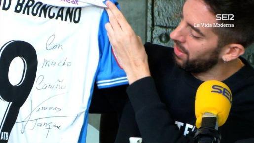 El presentador David Broncano mira la camiseta del Atlético Baleares con su nombre y dedicada por el delantero blanquiazul Vinicius Tanque.