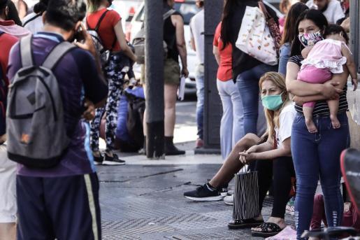 Varias personas hacen cola para solicitudes de trabajo en Buenos Aires.