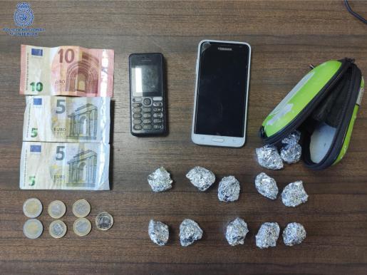 Entre las pertenencias de uno de los detenidos los agentes hallaron dos teléfonos móviles y dinero en efectivo, así como 13 envoltorios conteniendo en su interior una sustancia verde vegetal, al parecer marihuana.