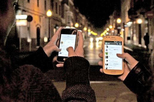 Dos adolescentes manejan chats en sus respectivos teléfonos móviles.