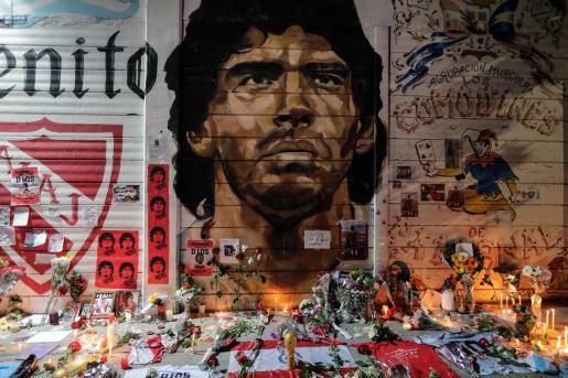 Fotografía de las ofrendas florales, banderas, velas y cartas que adornan a modo de altar un mural con la imagen de Diego Armando Maradona.
