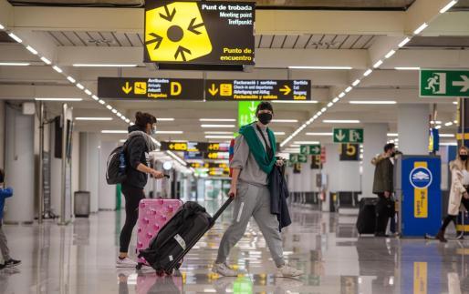 Viajeros caminan por la terminal de llegadas del aeropuerto de Palma.