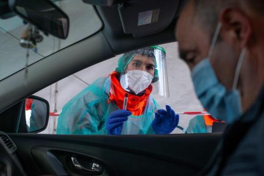 Una sanitaria realiza el test de saliva a un ciudadano durante un cribado selectivo de positivos por COVID-19.