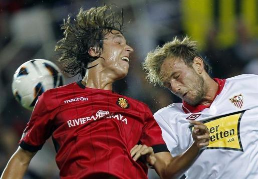 El centrocampista croata del Sevilla CF, Ivan Rakitic (d), salta por el balón con Tomás Pina, del RCD Mallorca.