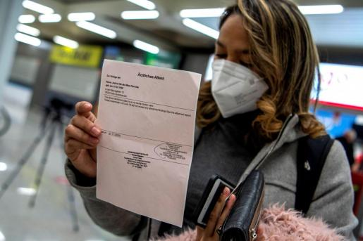 Una pasajera procedente de un vuelo de Colonia (Alemania) muestra el resultado negativo de su PCR, este lunes, tras aterrizar en el aeropuerto de Palma de Mallorca.