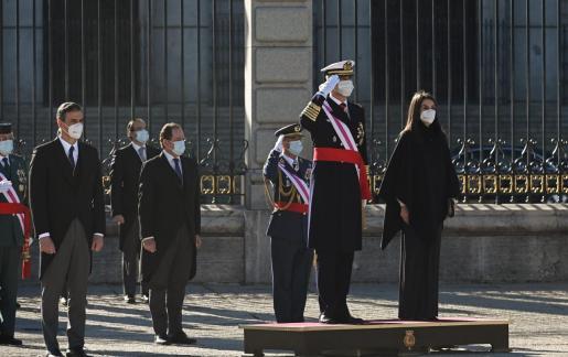El rey Felipe VI (2d), la reina Letizia (d), y el presidente del Gobierno, Pedro Sánchez (i), escuchan el Himno Nacional durante la ceremonia de la Pascua Militar celebrada, este miércoles, en el Palacio Real en Madrid.
