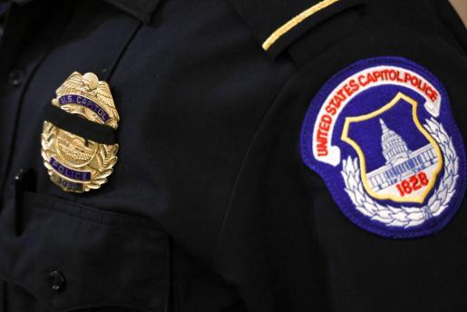 Una agente de policía del Capitolio lleva un crespón negro por la muerte del agente Brian Sicknick.