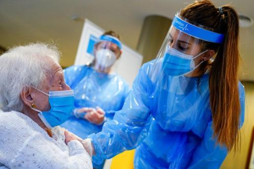 Personal sanitario vacunando a una usuaria de na residencia en Madrid.