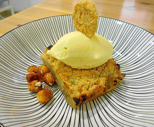 Una excelente versión de crumble de manzana servido con helado y adornado con una galletita y unos anacardos fritos con azúcar.
