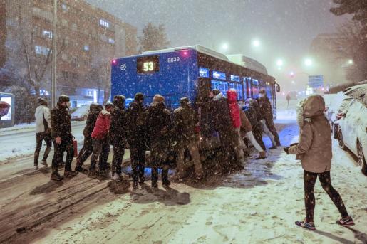 Varias personas empujan un autobús bajo una intensa nevada en la avenida Ramón y Cajal, en Madrid.