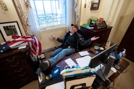 El seguidor de Donald Trump sentado en el escritorio de la presidenta de la Cámara de Representantes de Estados Unidos, Nancy Pelosi.