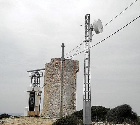 Un radar y una antena junto a la torre de defensa.